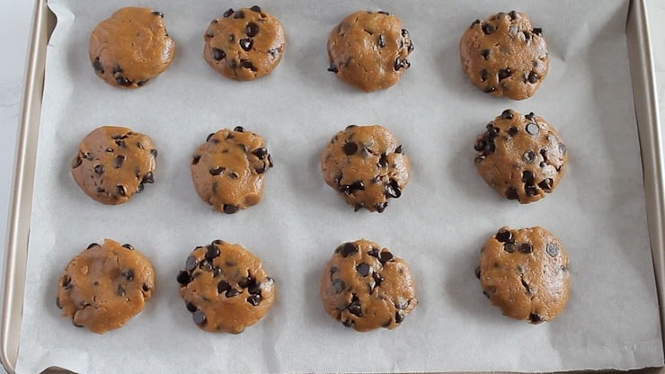 Overhead view of uncooked keto chocolate chip cookies on baking sheet