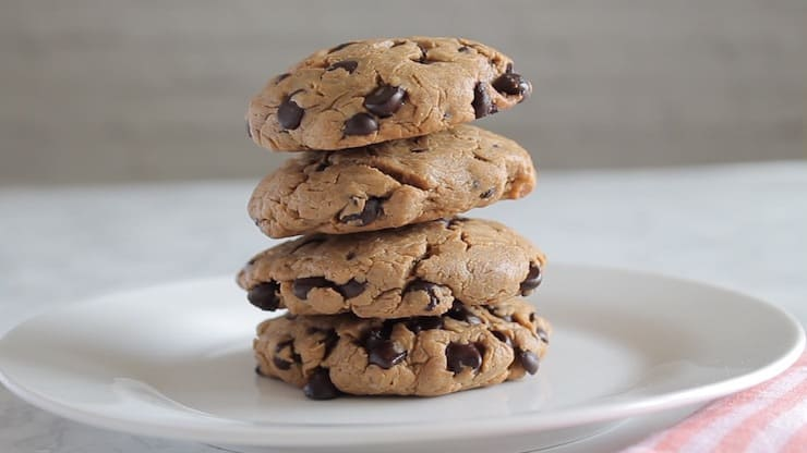 four keto chocolate chip cookies stacked on a white plate with white background