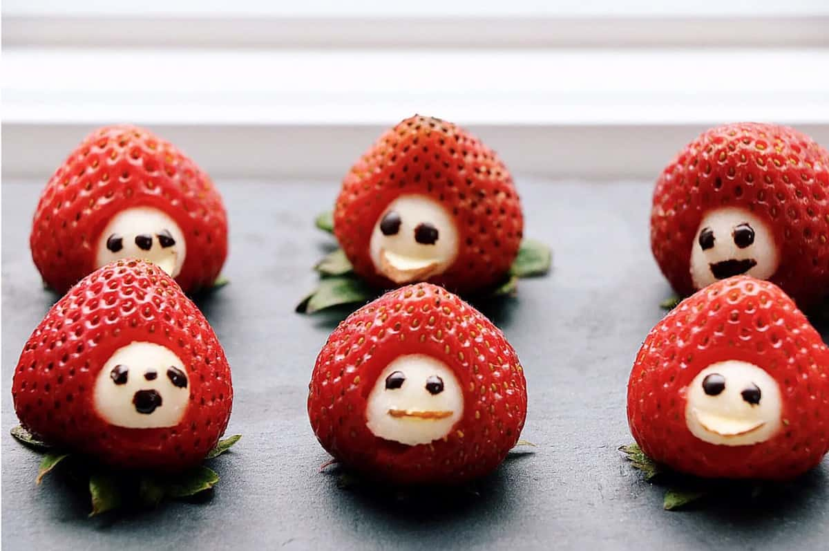six strawberries in a row with white spots on them with faces drawn on them
