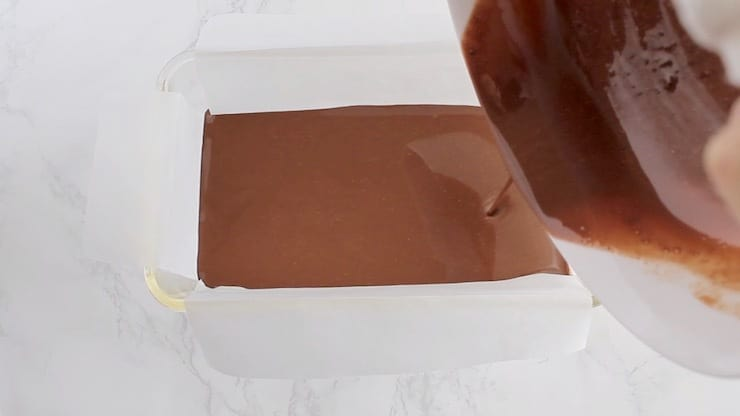 Keto fudge melted ingredients being poured into a glass loaf pan lined with white parchment paper