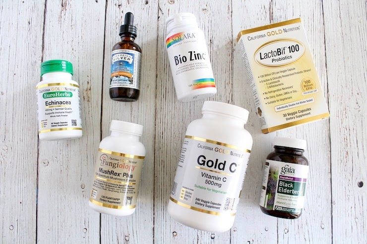 overhead view of bottles of the best supplements to boost the immune system laying flat on white wooden table