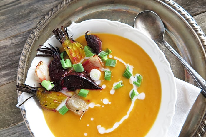 White bowl filled with orange creamy butternut soup drizzled with white sauce with root vegetables inside