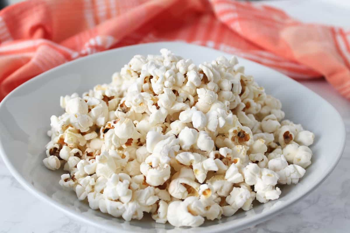 Popped popcorn in a white shallow bowl on a white marble surface next to a red and white plaid dish cloth