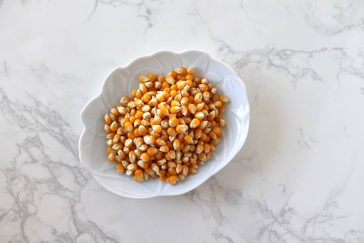 Small white dish with popcorn kernels in it on a white marble surface