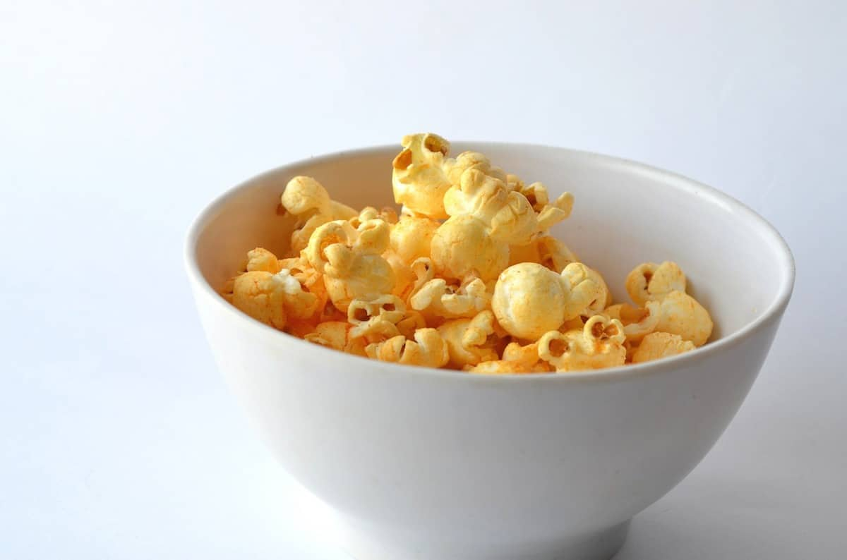 Popcorn in a white bowl on a white surface