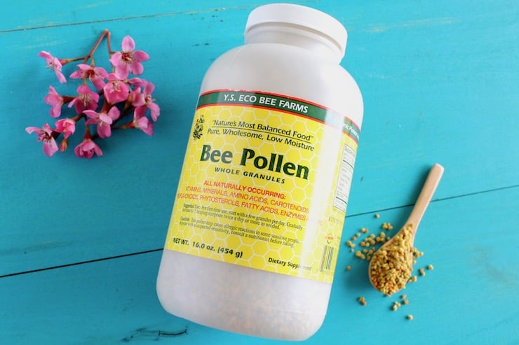 Large bottle of bee pollen next to pink flowers and spoon of bee pollen granules on blue wooden surface