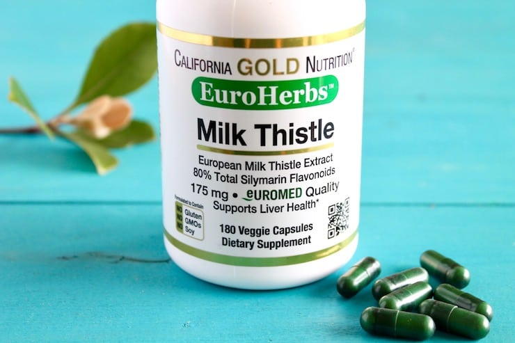 Bottle of milk thistle capsules next to green leaves and green capsules on blue wooden surface