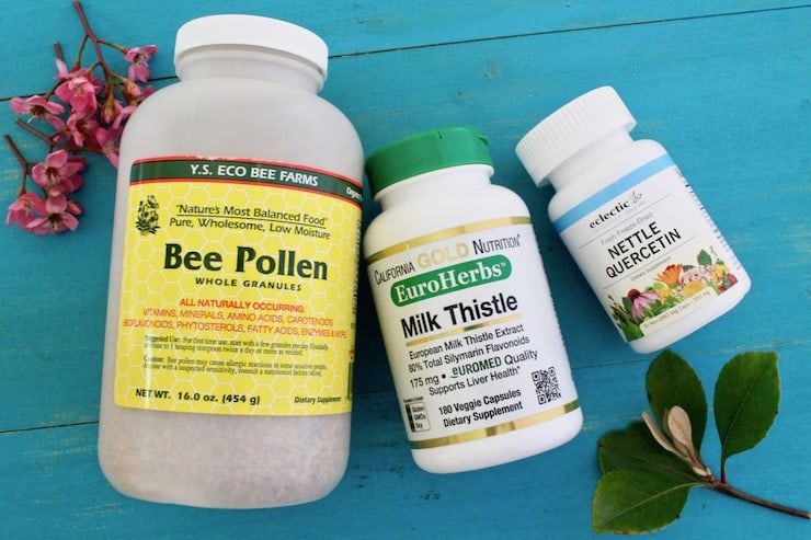 Bottles of bee pollen, milk thistle and nettle quercetin next to each other on a blue wooden surface