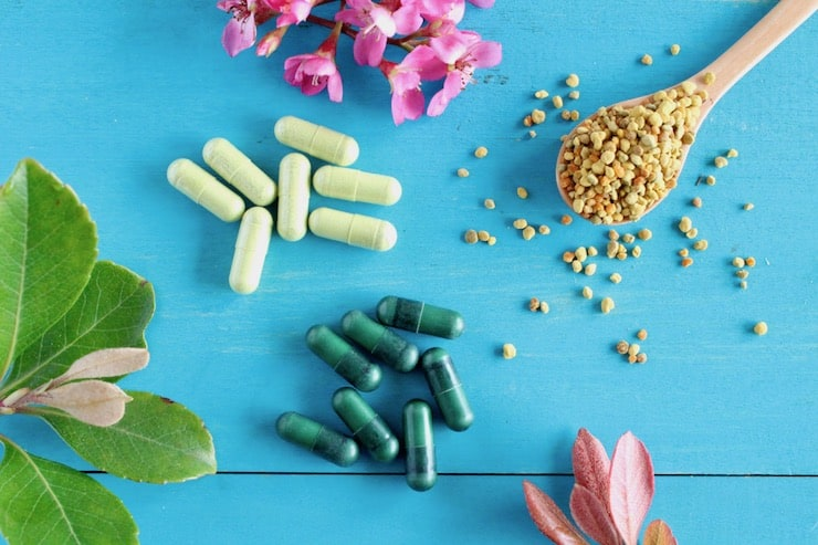 Wooden spoon full of bee pollen next to light and dark green vitamin capsules on a blue wooden surface