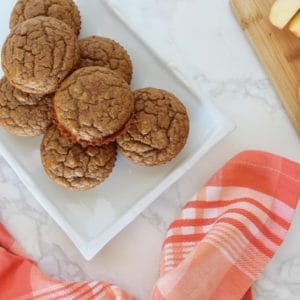 Overhead view of six applesauce muffins on a white plate next to a red and white plaid napkin