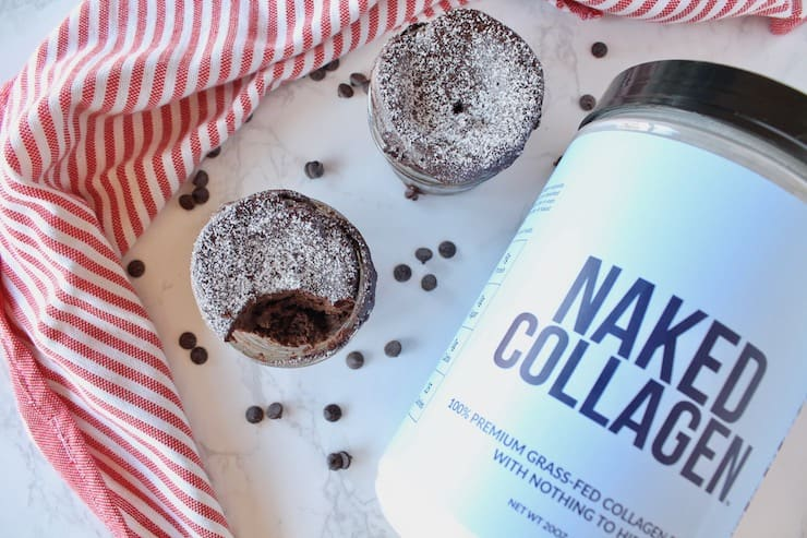 2 jars of finished chocolate keto mug cakes one with a bite taken out of it on a white surface sprinkled with chocolate chips next to a red and white striped dish towel and a blue tub of naked collagen