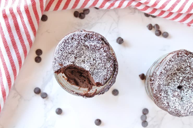 2 jars of finished chocolate keto mug cakes one with a bite taken out of it on a white surface sprinkled with chocolate chips next to a red and white striped dish towel