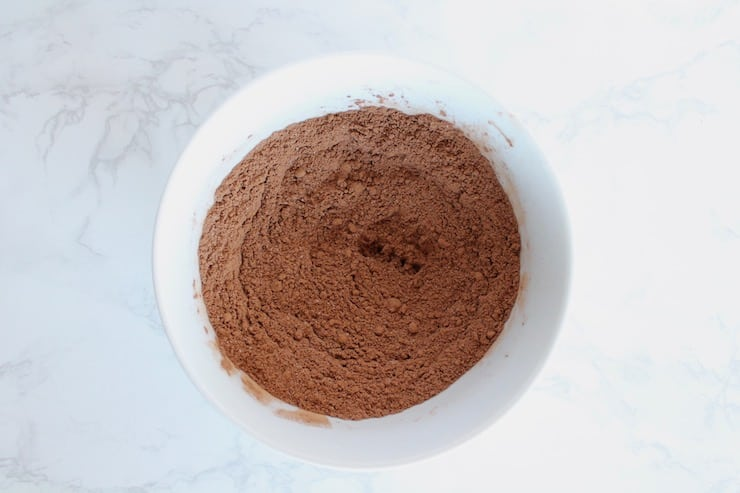 Chocolate keto mug cake mixed dry ingredients in a white bowl on a white marble surface