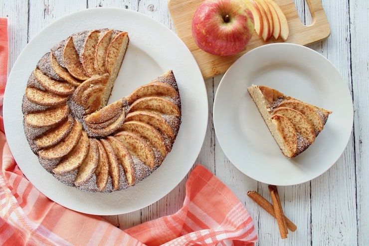Overhead view of apple cake on a white plate with a slice out of it next to smal white plate with slice of apple cake on it