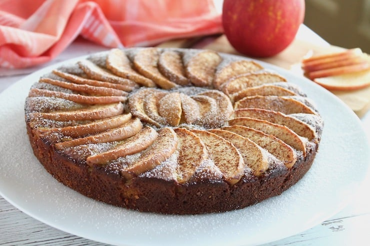 Whole apple cake with arranged apple slices on top on a white plate with an apple in the background next to red and white plaid dish towel