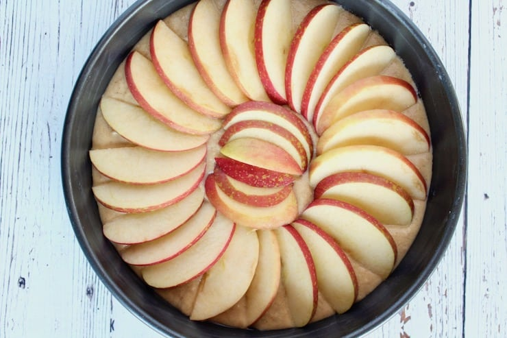 Uncooked apple cake in metal cake pan on a white wooden table
