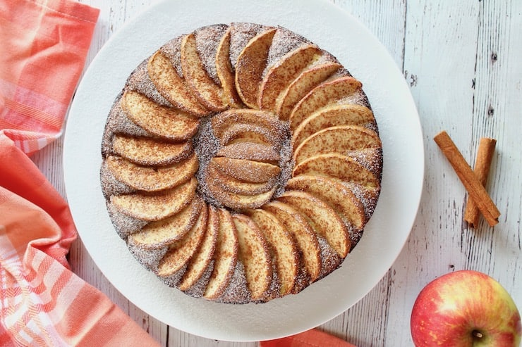Overhead view of whole apple cake with arranged apple slices on top on a white plate with an apple in the background next to red and white plaid dish towel