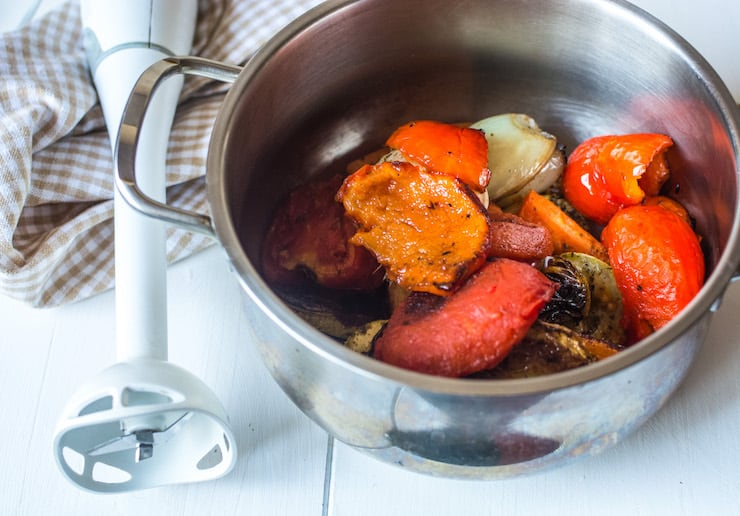Roasted vegetables in a metal bowl on a white wooden surface with an immersion blender sitting next to it