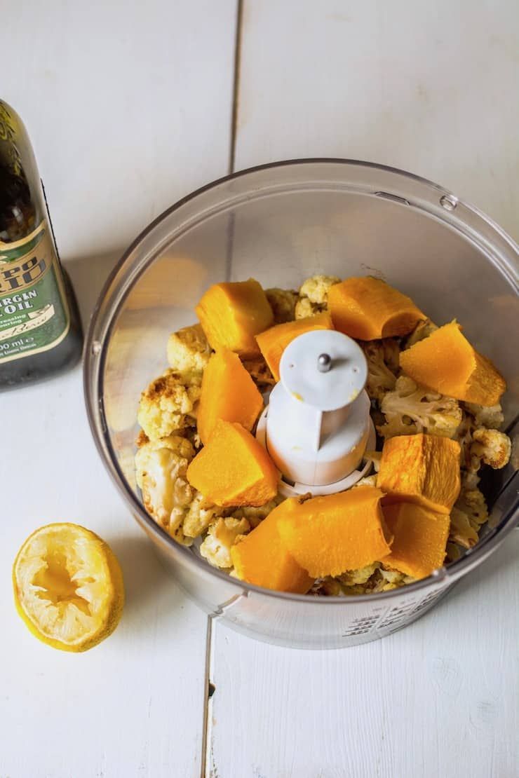 Roasted cauliflower and pumpkin cubes in a food proessor on a white wooden table next to half of a lemon and an olive oil bottle