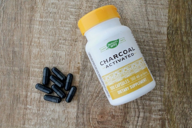 White and yellow supplement bottle of activated charcoal on wooden table next to black capsules of charcoal