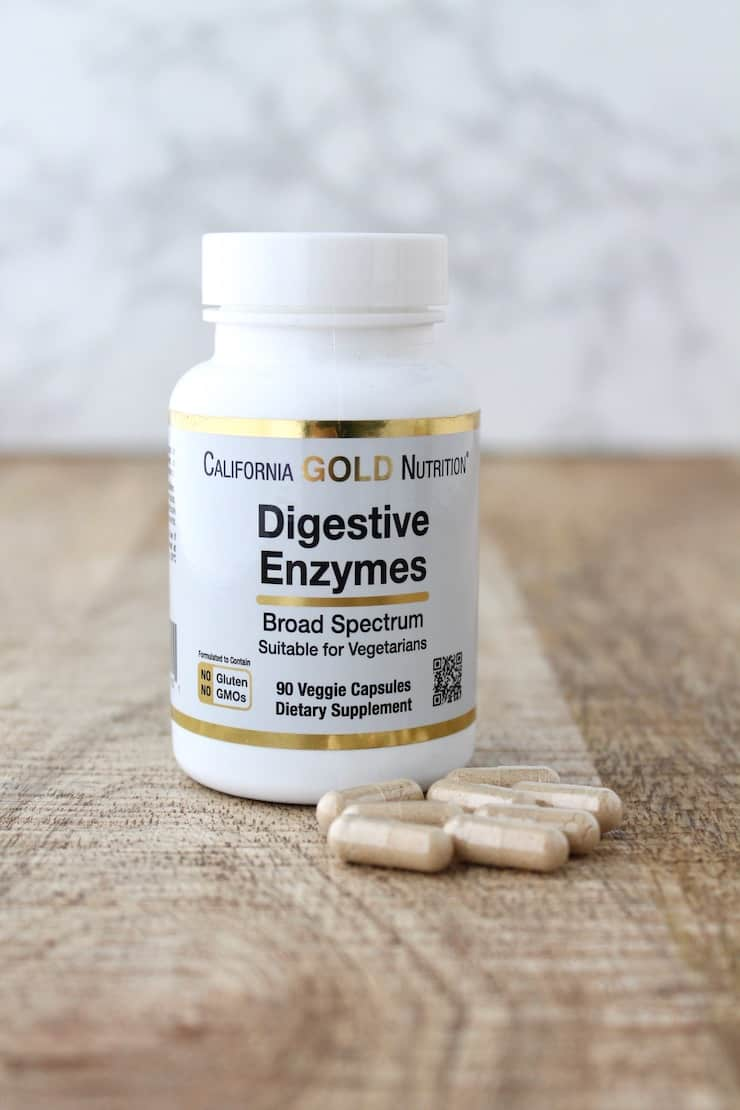 White supplement bottle of digestive enzymes next to capsules on a wooden table