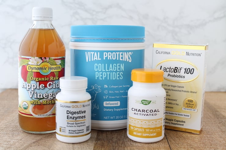 Glass bottle of apple cider vinegar next to a blue tub of vital proteins collagen peptides, Lactobif 100 probiotics box, white bottle of digestive enzymes and yellow and white bottle of activated charcoal on a wooden table with a marble background
