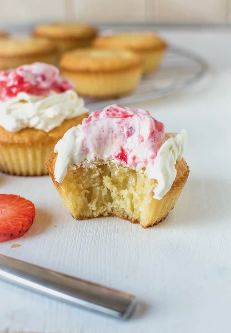 Close up of yellow cupcake with a bite taken out of it with white frosting on top with strawberry puree on top on white surface with cupcakes in the background and strawberry slices next to it