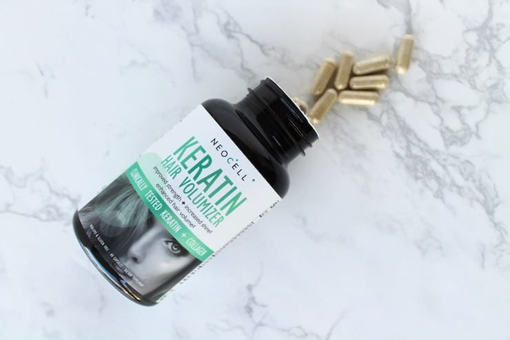 Keratin supplement bottle laying flat on a white marble surface with capsules spilling out of the bottle