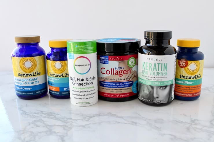 A collection of different supplement bottles for hair growth sitting on a white marble surface