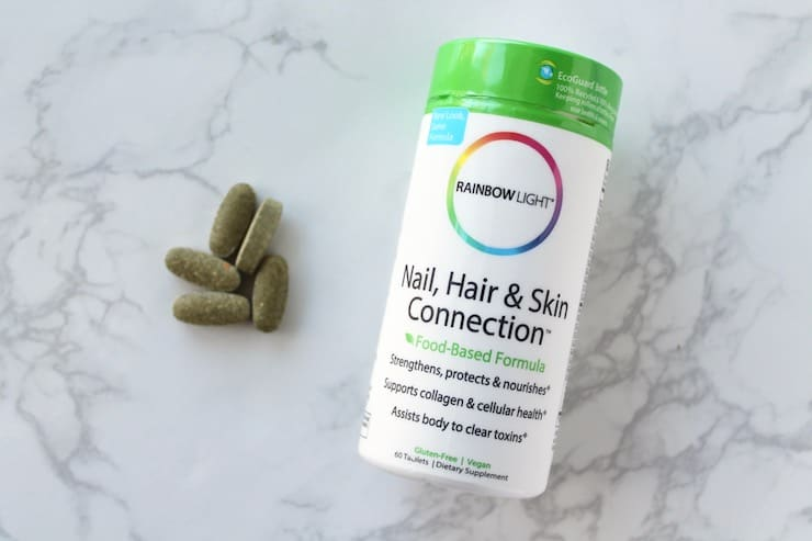 Supplement bottle of nail, hair and skin vitamins laying flat on a white marble surface next to vitamin tablets