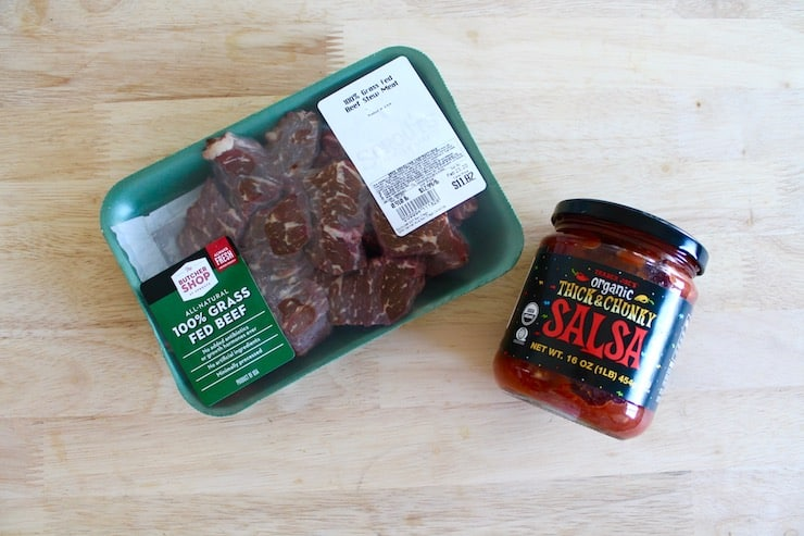 A package of grass fed beef stew meat and a jar of salsa on a wooden table