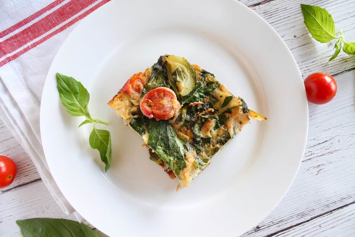 Square slice of turkey veggie baked frittata on a white plate on a white wooden surface with a red a white striped dish towel next to it