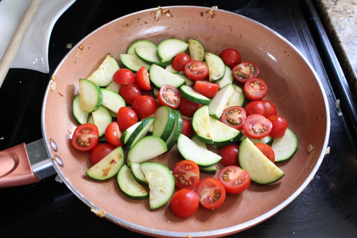 sliced zucchini and tomatoes in a sauté pan on the stove