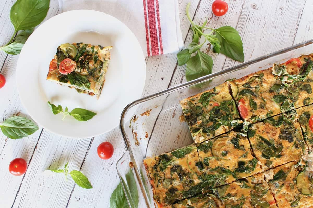 Square slice of turkey veggie baked frittata on a white plate on a white wooden surface with cherry tomatoes and basil next to it with the full frittata dish next to it