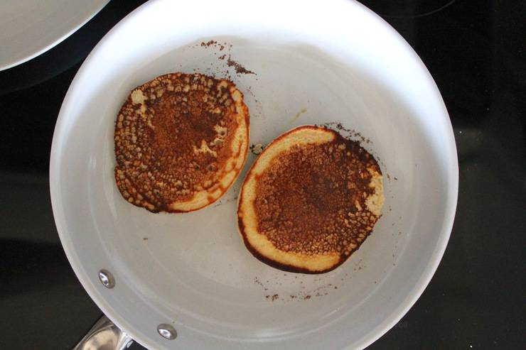 Overhead view of skillet with flipped pancakes cooking