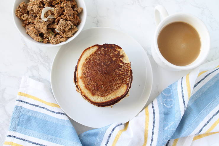 Overhead view of father's day breakfast with a white plate of stacked pancakes, white bowl filled with granola and a white mug filled with coffee and creamer on a white marble surface with a blue, white and yellow striped kitchen towel