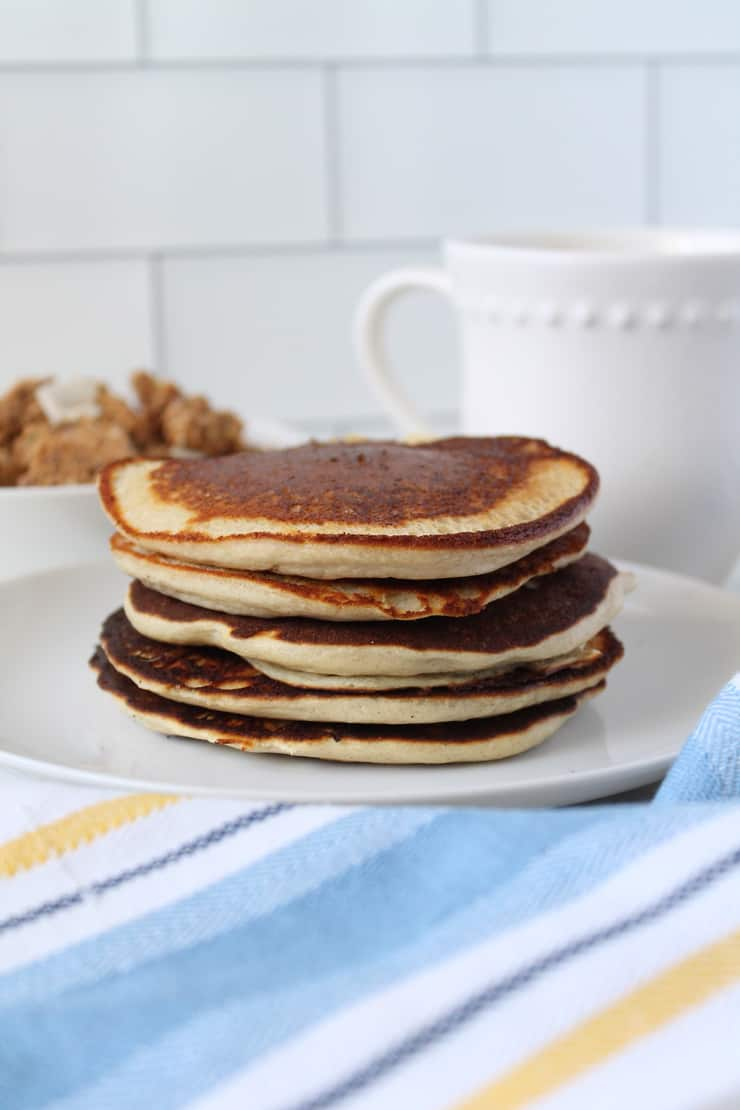 Close up of stacked pancakes on a white plate with a blue, white and yellow striped kitchen towel next to it with a white bowl filled with granola and a white mug in the background on a white marble surface