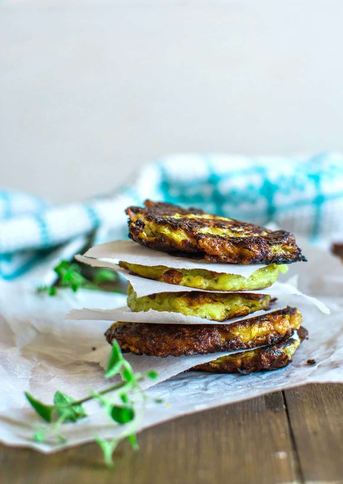 gluten free zucchini fritters stacked on top of each other with parchment paper in between on a brown wooden table with green herbs next to it
