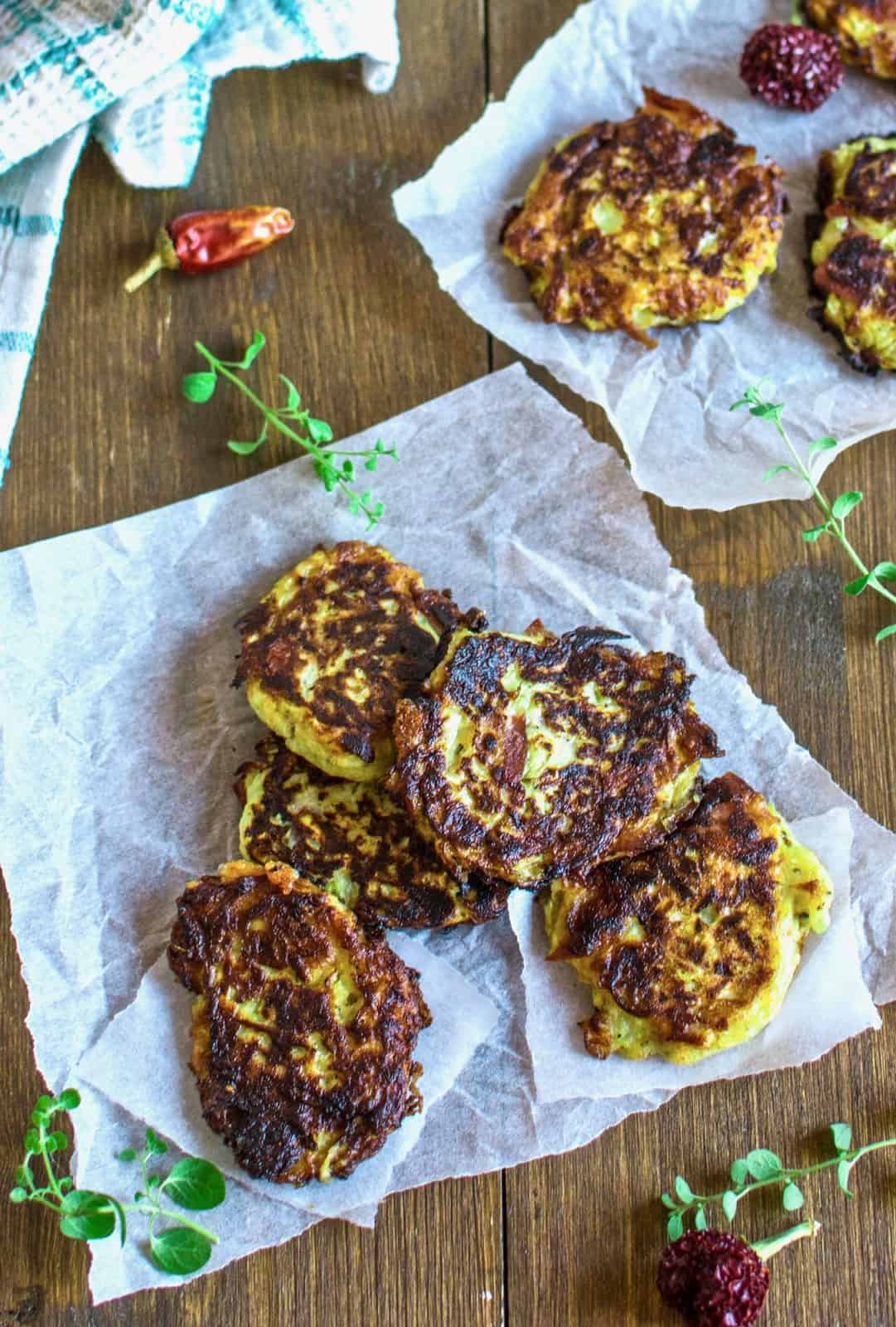 several zucchini fritters laid out on white parchment paper on a brown wooden table with green herbs next to it