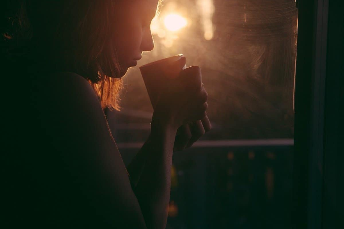 silhouette of a woman drinking a mug of tea with sun at dusk shining through a window
