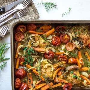 Sheet pan filled with herb roasted chicken and vegetables on a white wooden table next to a napkin with knives and forks on it next to herb sprigs