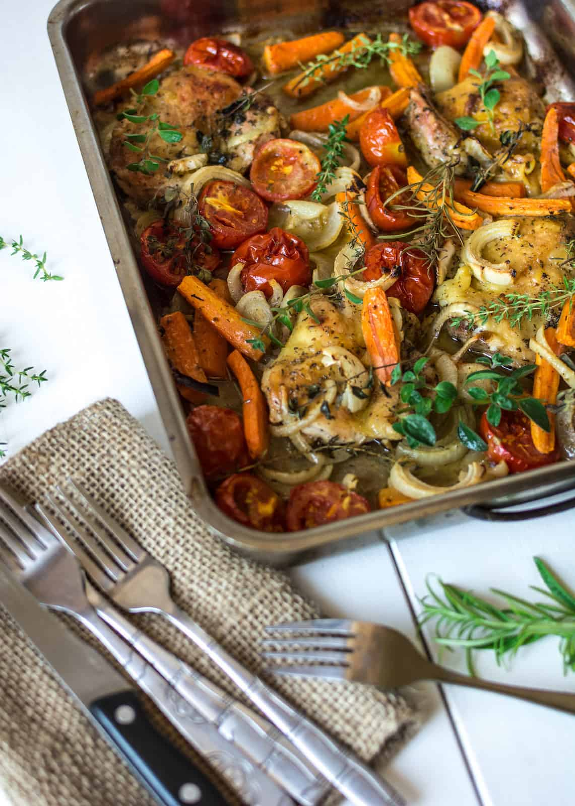 Close up of sheet pan filled with herb roasted chicken and vegetables on a white wooden table next to a napkin with knives and forks on it next to herb sprigs