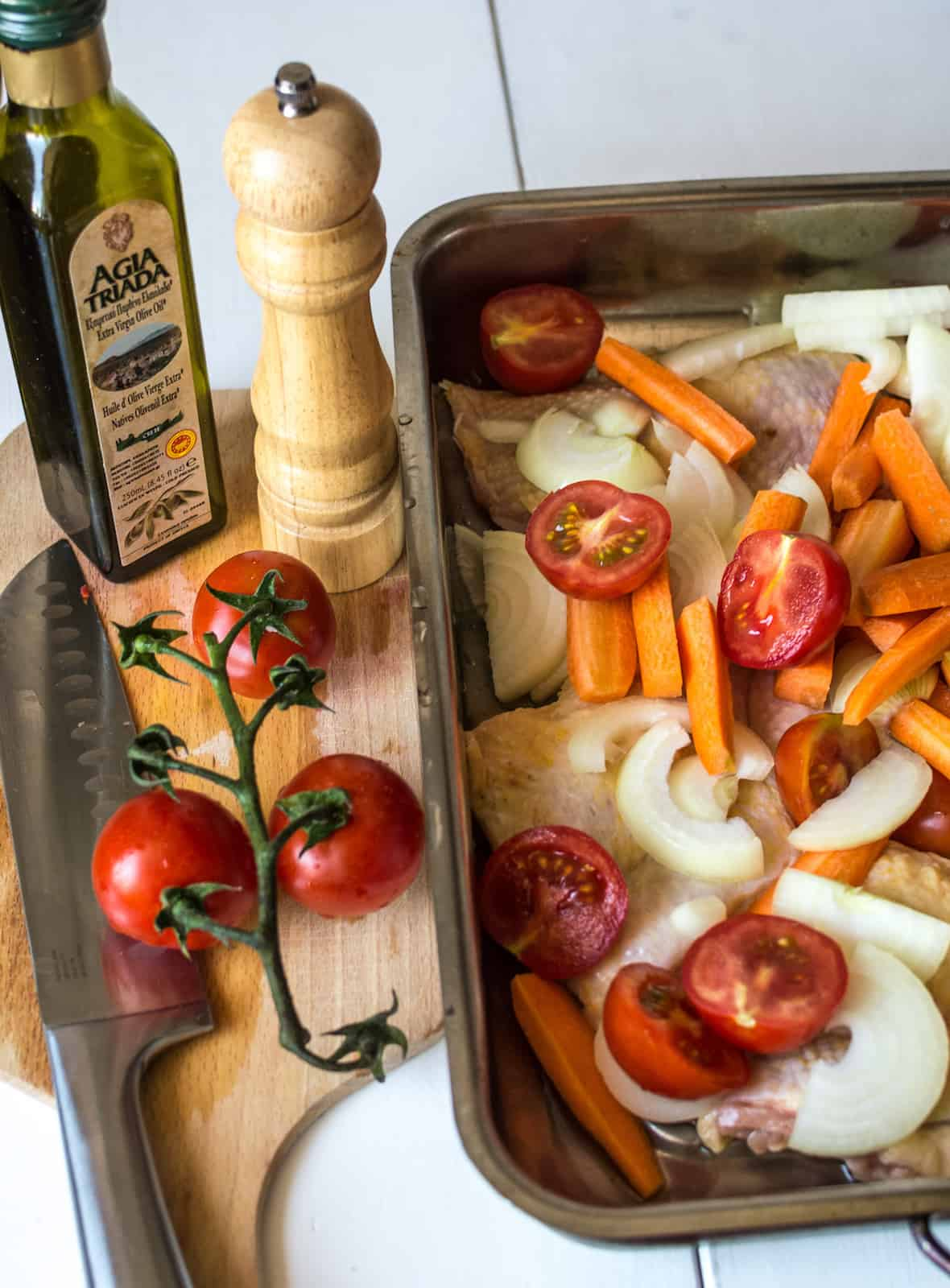 Uncooked chicken and vegetables in a sheet pan next to a cutting board with a chefs knife, tomatoes, olive oil and a pepper grinder on it