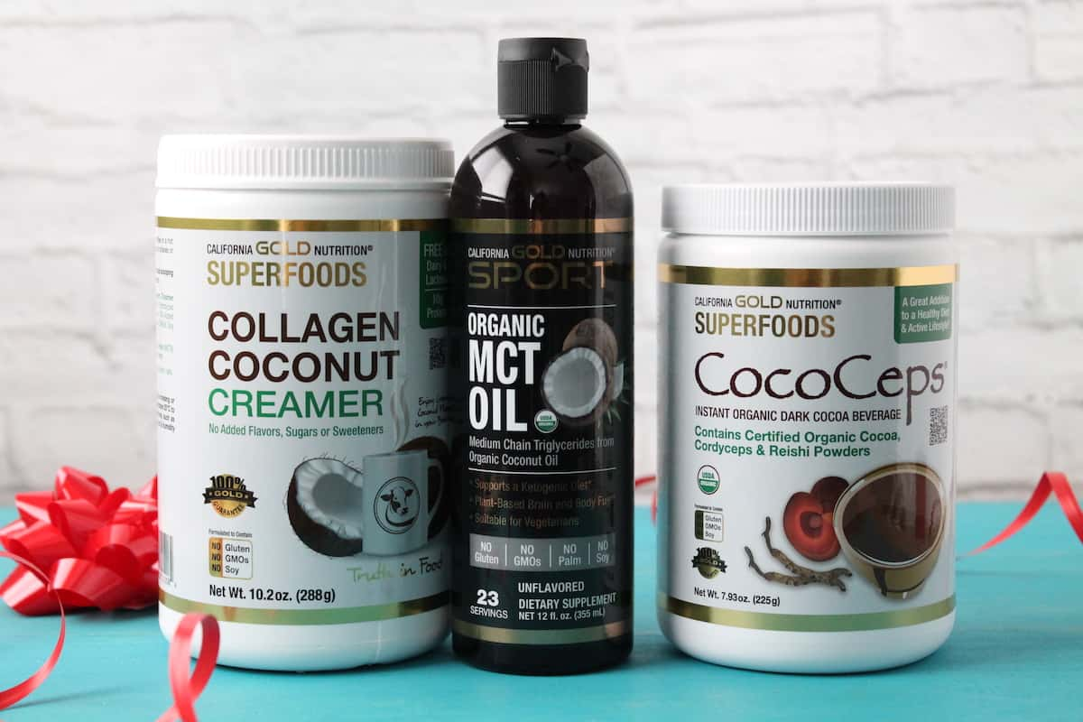 tub of collagen coconut creamer, mct oil and cococeps on a teal wooden surface with a white brick background next to a red ribbon