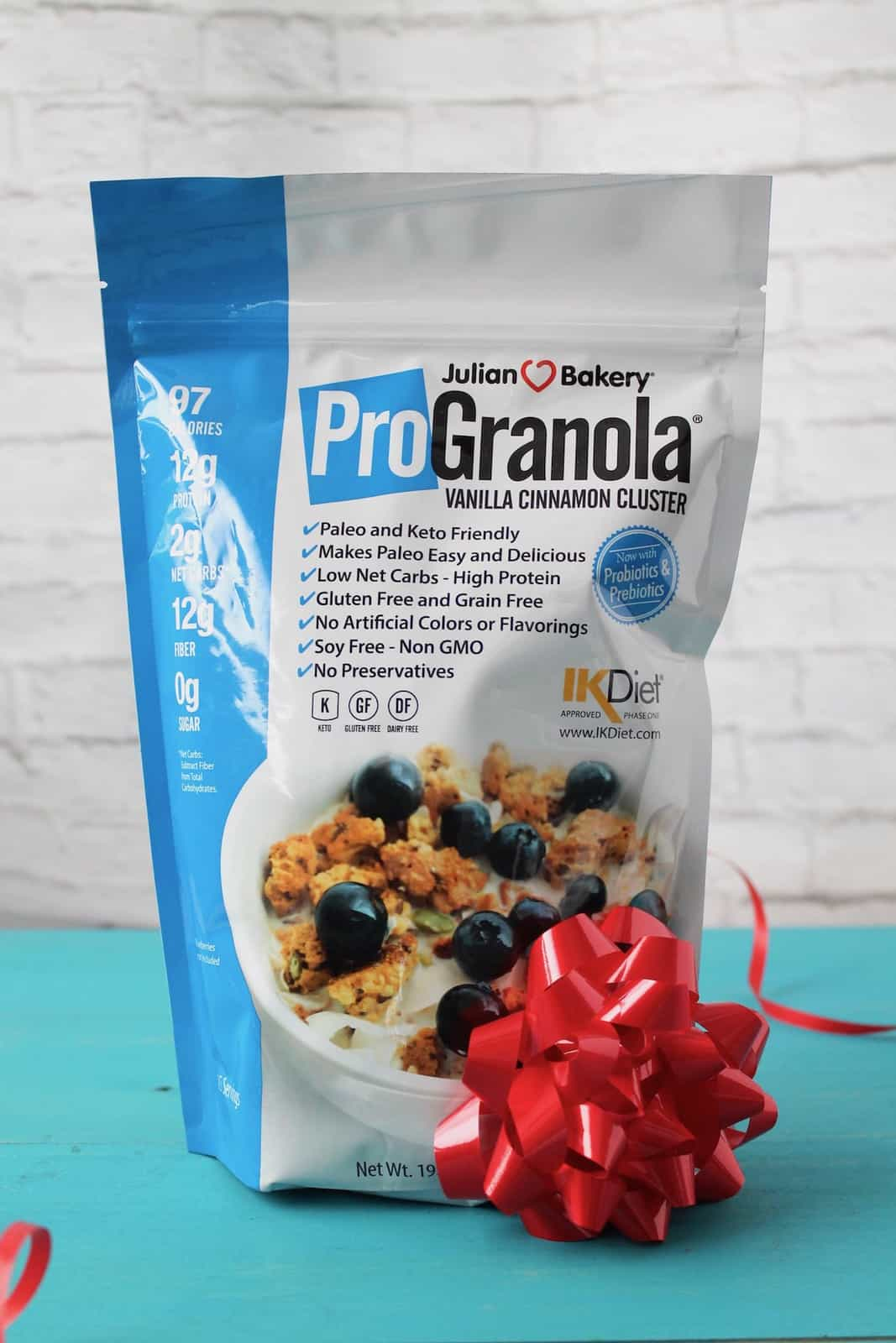 blue and white bag of keto granola with a red bow on it on a teal wooden table with a white brick background