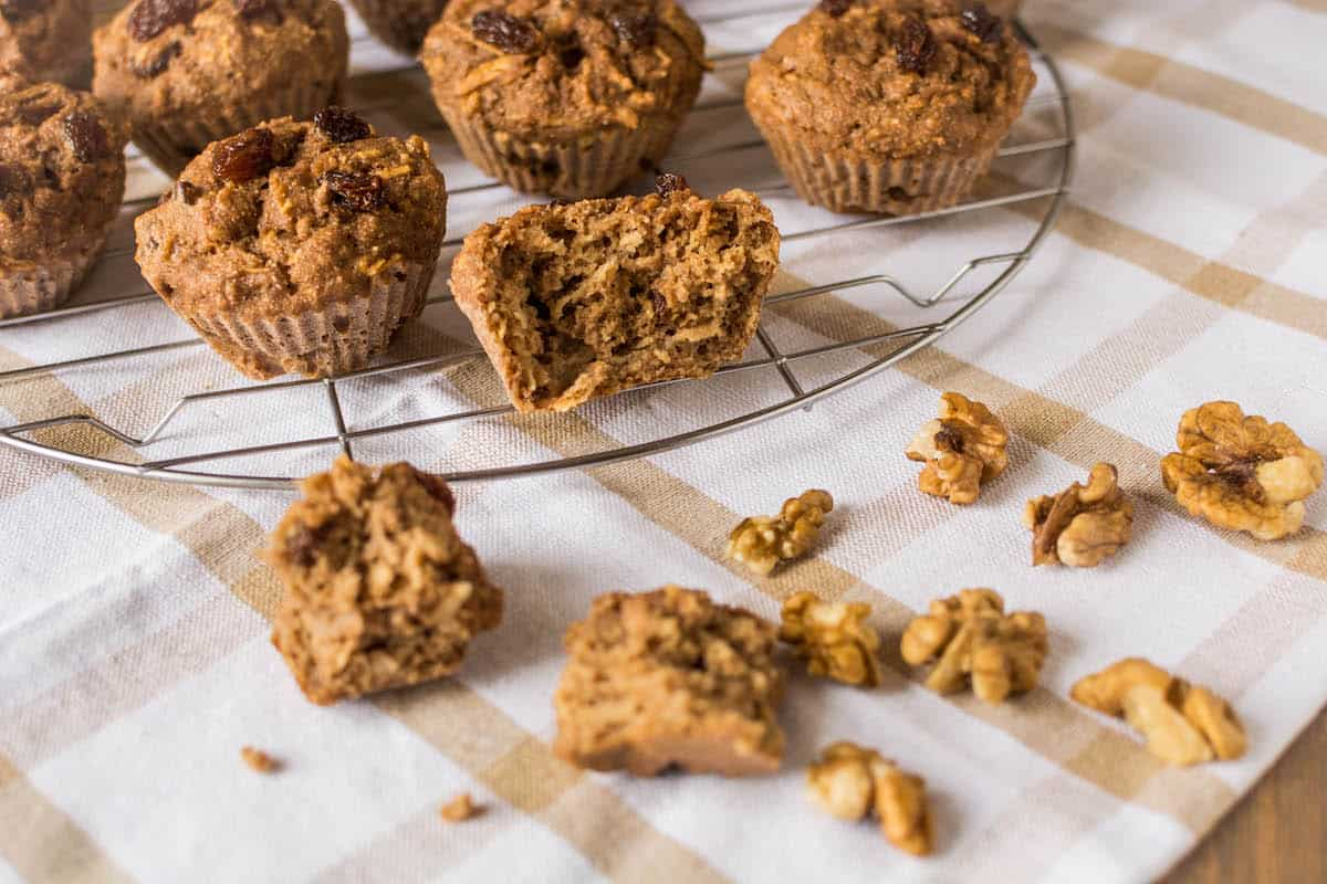 Apple muffin halved on a wire cooling rack next to whole muffins over a white and brown dish towel