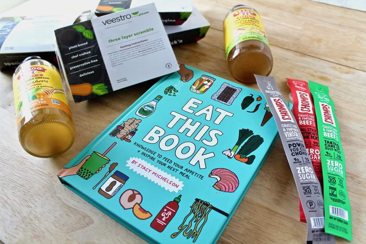 Veestro meal boxes, Braggs drinks, A book called 'eat this book' and various chomps jerky sticks on a blonde wooden surface