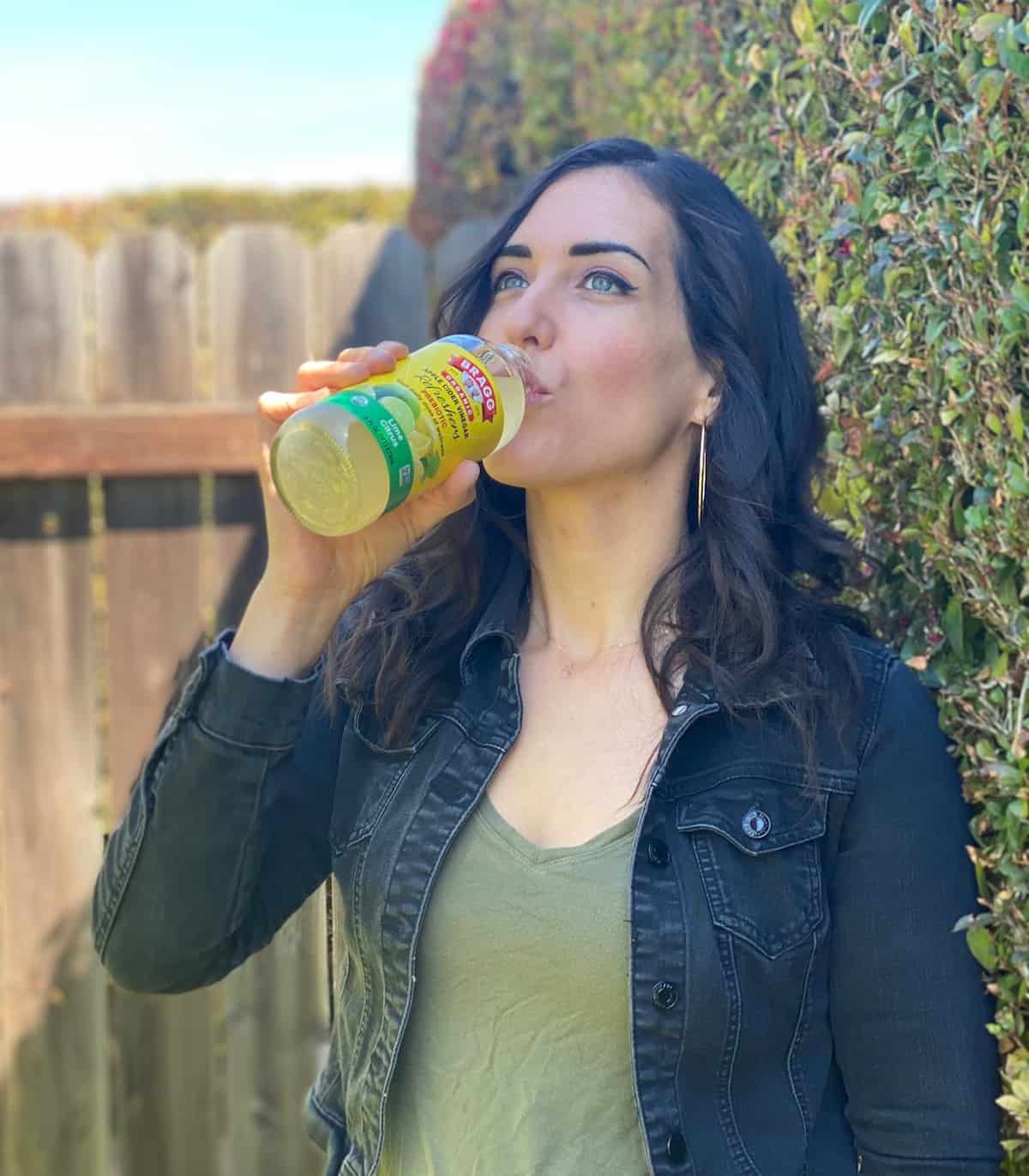 Dark haired woman with green shirt and black jean jacket standing outside drinking a drink