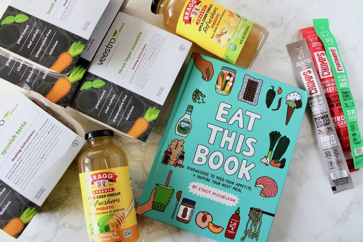 Veestro meal boxes, Braggs drinks, A book called 'eat this book' and various chomps jerky sticks on a white marble surface
