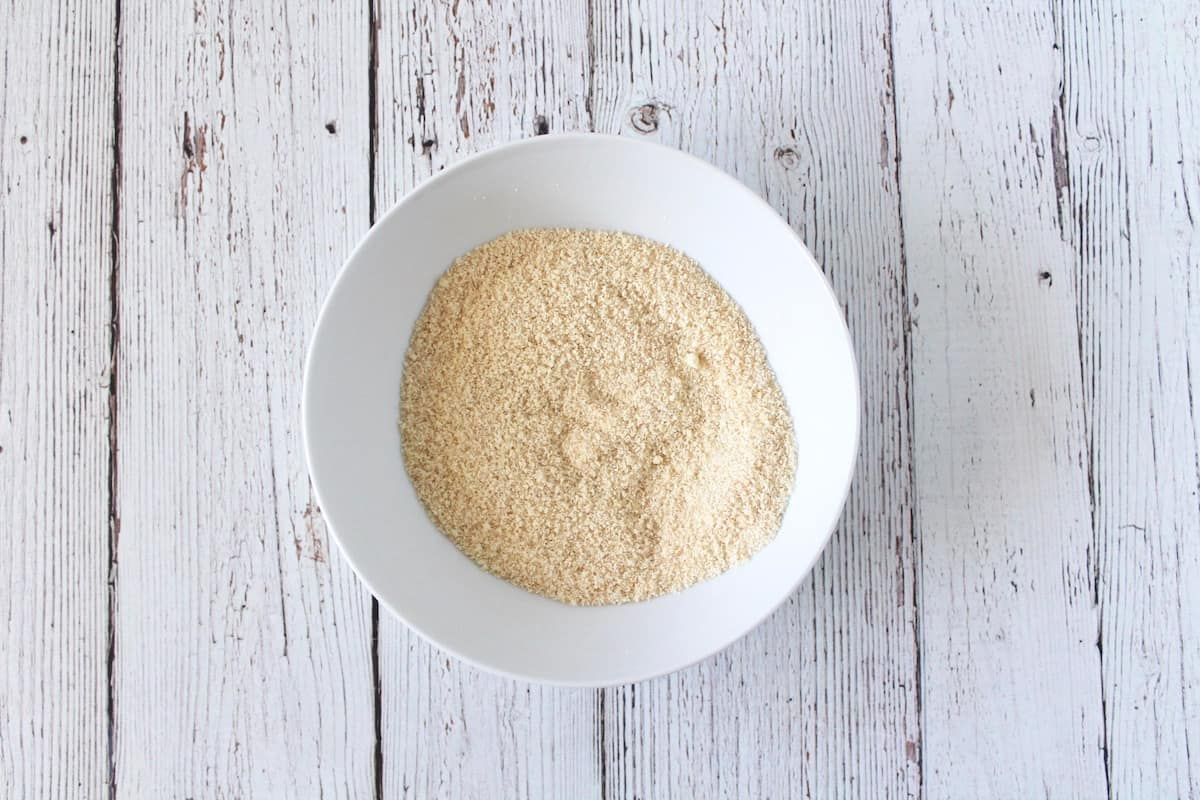 Overhead shot of mug cake dry ingredients in a white bowl on a white wooden surface